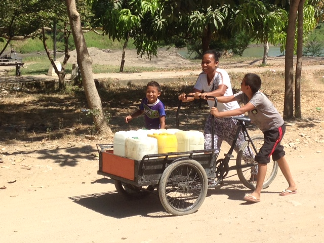 One family uses the tricycle transport to ship water to their neighborhood in Mompos